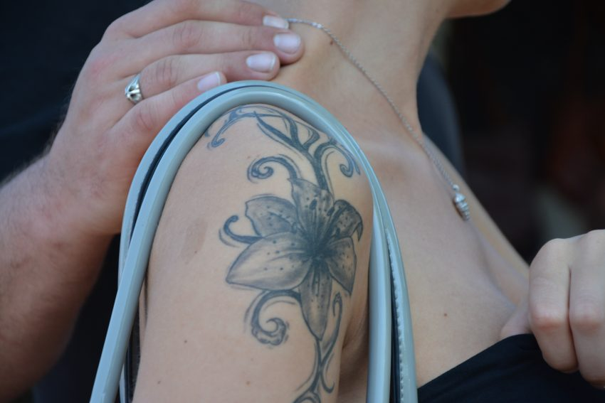 woman with black and white floral tattoo on her right shoulder